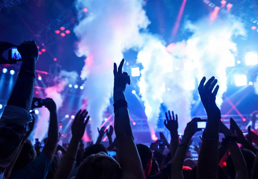 Hands in the air at a concert with stage in background