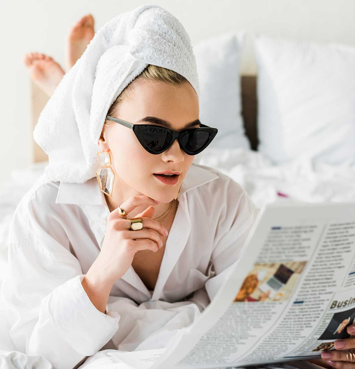 Woman in bed reading newspaper