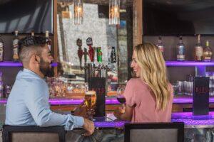 Man and woman laughing at a bar